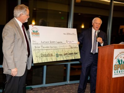 Alumni President, Steve Parks presents a whopping $9,000.00 Alumni check to Antioch Sports Legends Tom Lamothe accepts.