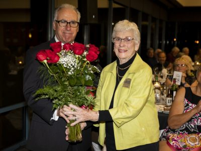 Executive Board member and Master of Ceremonies Gary Bras presents flowers of apprecation to Volunteer and Executive Board member Joanne Bilbo.